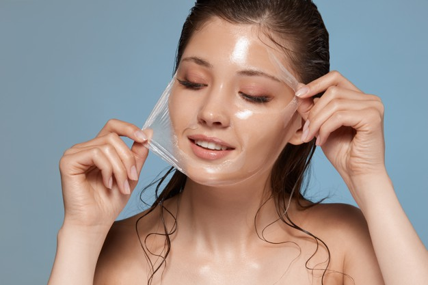 young-happy-woman-removes-facial-mask-looking-down-side_355000-3341